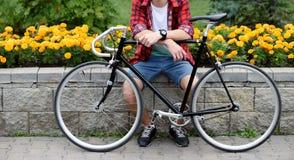 Hombre del inconformista con la bicicleta que descansa sobre macizo de flores Imagen de archivo libre de regalías