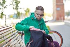 Hombre del inconformista con la mochila que se sienta en banco de la ciudad Fotos de archivo libres de regalías