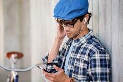 Hombre del inconformista con los auriculares, smartphone y la bici Foto de archivo libre de regalías