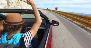 Hombre del inconformista con los brazos que agitan del sombrero que conducen en el enrrollamiento del camino costero en convertib metrajes
