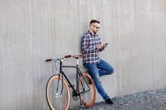 Hombre del inconformista en auriculares con smartphone y la bici foto de archivo