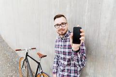 Hombre del inconformista en auriculares con smartphone y la bici Fotos de archivo