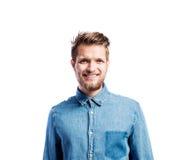 Hombre del inconformista en la camisa azul del dril de algodón, tiro del estudio, aislado Imagen de archivo