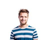 Hombre del inconformista en la camiseta azul rayada, tiro del estudio, aislado Imagen de archivo libre de regalías