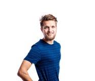 Hombre del inconformista en la camiseta azul rayada, tiro del estudio, aislado Foto de archivo libre de regalías
