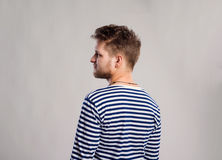 Hombre del inconformista en la camiseta rayada, fondo gris, tiro del estudio Foto de archivo libre de regalías