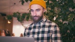 Hombre del inconformista en sombrero amarillo usando el ordenador portátil y el trabajo mientras que se sienta en el café o el es almacen de metraje de vídeo