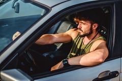 Hombre del inconformista que conduce un coche en un día soleado Fotografía de archivo libre de regalías