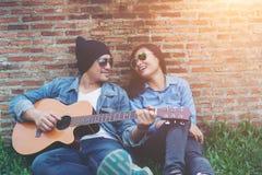 Hombre del inconformista que toca la guitarra para su novia al aire libre contra el Br Foto de archivo