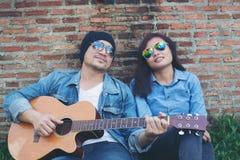 Hombre del inconformista que toca la guitarra para su novia al aire libre contra el Br Imagenes de archivo