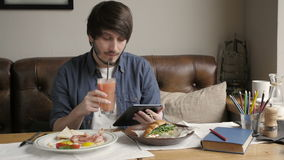 Hombre del inconformista que usa la tableta de Digitaces que come el desayuno sano almacen de metraje de vídeo