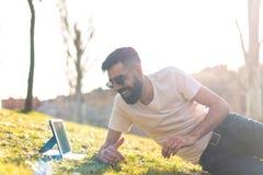 Hombre del inconformista usando una tableta digital en un parque fotografía de archivo
