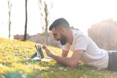 Hombre del inconformista usando una tableta digital en un parque fotos de archivo