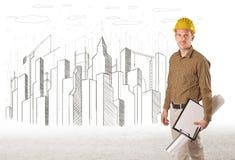 Hombre del ingeniero con el dibujo de la ciudad del edificio Fotografía de archivo libre de regalías