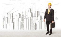Hombre del ingeniero de negocio con el dibujo de la ciudad del edificio en fondo Fotografía de archivo libre de regalías