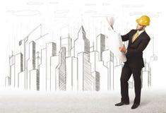Hombre del ingeniero de negocio con el dibujo de la ciudad del edificio en fondo Foto de archivo libre de regalías
