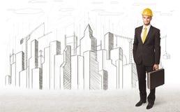 Hombre del ingeniero de negocio con el dibujo de la ciudad del edificio en fondo Imagenes de archivo