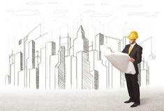 Hombre del ingeniero de negocio con el dibujo de la ciudad del edificio en fondo Imagen de archivo libre de regalías