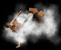 Hombre del karate que se rompe con el tablero de madera de la pierna foto de archivo libre de regalías