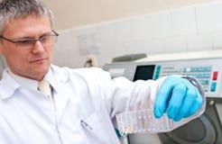 Hombre del laboratorio con los tubos de prueba Fotografía de archivo