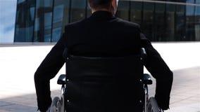 Hombre del lisiado en movimiento de la silla de ruedas cerca del centro de negocio moderno almacen de video