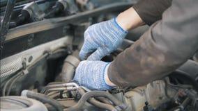 Hombre del mecánico en los guantes que reparan a las piezas de automóvil en la gasolinera metrajes