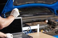 Hombre del mecánico que hace diagnóstico del coche del ordenador imagenes de archivo