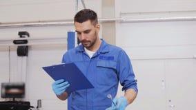 Hombre del mecánico con la llave que repara el coche en el taller 62 almacen de video
