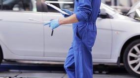 Hombre del mecánico con la llave que repara el coche en el taller 40 almacen de metraje de vídeo