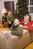 hombre del Mediados de-adulto y padres mayores por el árbol de navidad imagen de archivo libre de regalías
