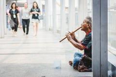 Hombre del mendigo con la flauta que pide dinero en la calle Imágenes de archivo libres de regalías