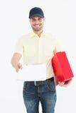 hombre del mensajero con la caja roja que da el tablero Foto de archivo libre de regalías