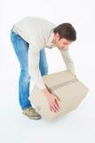 Hombre del mensajero que coge la caja de cartón Fotografía de archivo libre de regalías