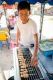 Hombre del mercado que vende el cerdo asado a la parrilla. Imagenes de archivo