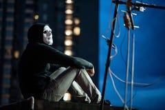 Hombre del misterio en la máscara blanca que se sienta en tejado foto de archivo libre de regalías