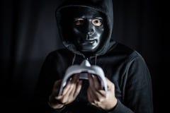 Hombre del misterio en la máscara negra que lleva a cabo la máscara blanca imagen de archivo libre de regalías