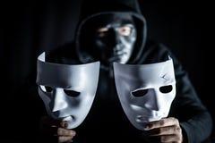 Hombre del misterio en la máscara negra que lleva a cabo las máscaras blancas fotos de archivo libres de regalías