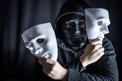 Hombre del misterio en la máscara negra que lleva a cabo las máscaras blancas fotos de archivo