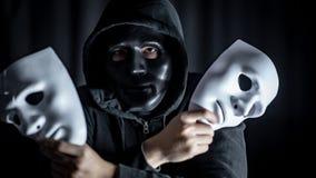 Hombre del misterio en la máscara negra que lleva a cabo las máscaras blancas imagenes de archivo