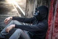 Hombre del misterio en la máscara negra que se sienta en la sensación constructiva abandonada foto de archivo libre de regalías