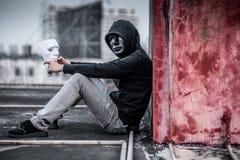 Hombre del misterio en la máscara negra que siente presionada llevando a cabo la máscara blanca imagen de archivo libre de regalías