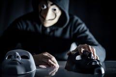 Hombre del misterio que elige la máscara en la tabla fotos de archivo