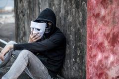 Hombre del misterio que saca la máscara que muestra otra máscara bajo ella imagen de archivo libre de regalías
