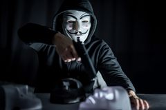 Hombre del misterio que sostiene el arma sobre la máscara blanca fotografía de archivo