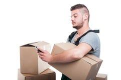 Hombre del motor que sostiene la caja de cartón y que manda un SMS a smartphone Fotos de archivo libres de regalías