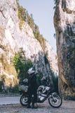 Hombre del motorista en la moto de la aventura en el camino de la montaña en el barranco de Bicaz, Rumania Concepto del turismo y foto de archivo libre de regalías