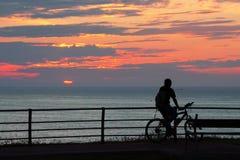 Hombre del motorista que ve la puesta del sol imagen de archivo