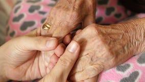 hombre del nieto que lleva a cabo la mano muy de la vieja abuela mayor de la mujer almacen de metraje de vídeo