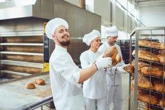 Hombre del panadero que sostiene el pan fresco en una panadería imagenes de archivo