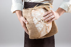 Hombre del panadero que sostiene la barra de pan orgánica rústica en manos Fotografía de archivo